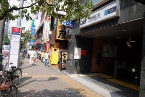 新宿西口駅なめの向こうにカラオケ館看板